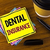 Dental insurance written on yellow note paper
