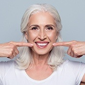 Older woman pointing to healthy smile