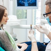 Dentist showing woman an implant model