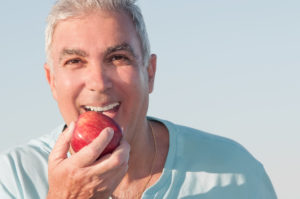 man smiling holding apple